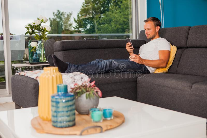 发短信与他的电话和变冷在长沙发的严肃的看的人 库存照片