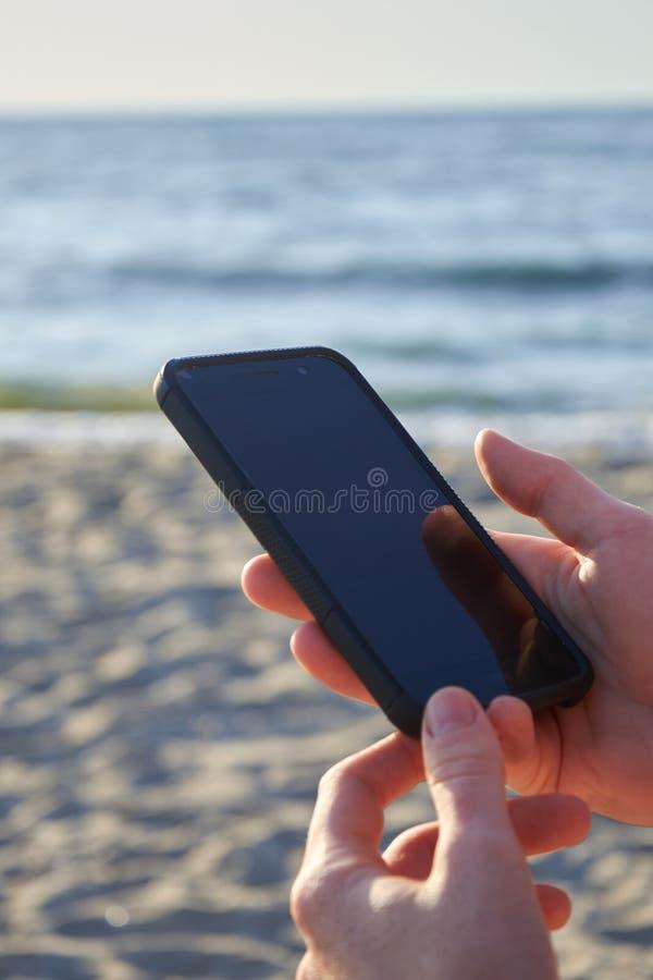 发短信与她的在海滩的手机消息的逗人喜爱的微笑的女孩 好放松 库存照片