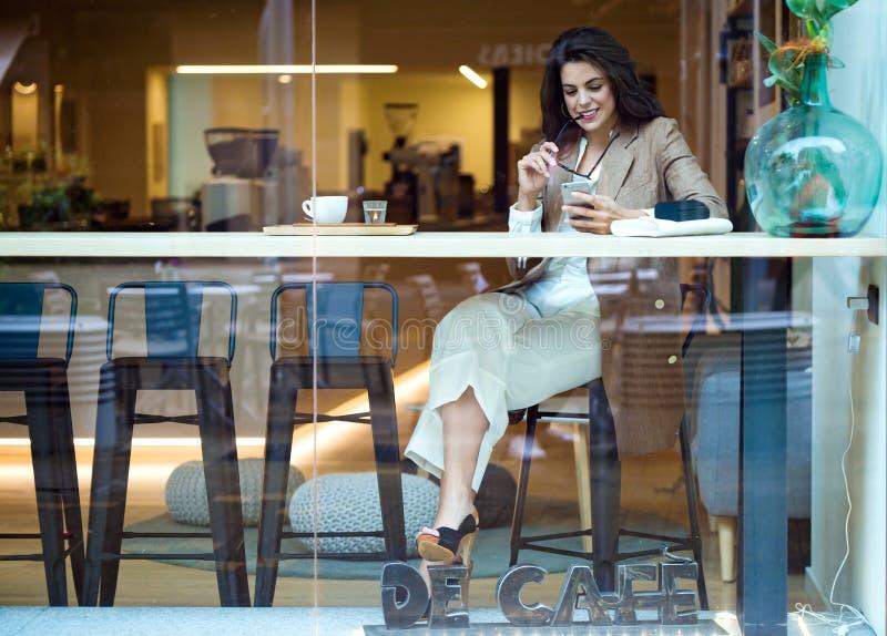 发短信与她的手机的可爱的年轻女实业家在咖啡馆 免版税图库摄影