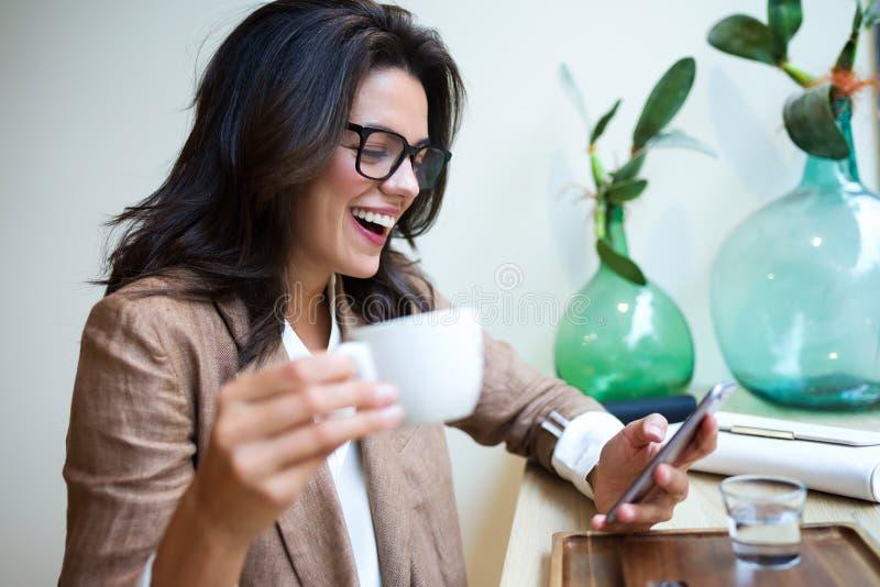 发短信与她的手机的笑的年轻女实业家在咖啡馆 库存图片