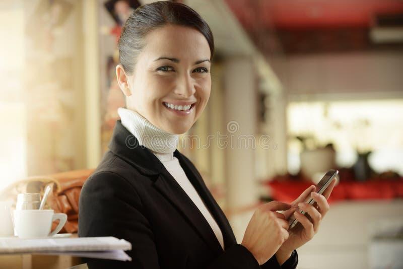 发短信与她的手机的酒吧的妇女 免版税库存图片
