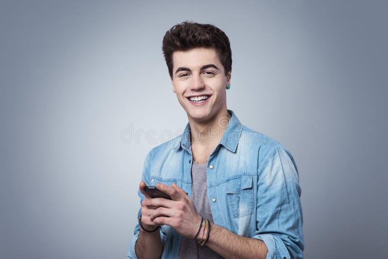 发短信与智能手机的微笑的人 库存照片
