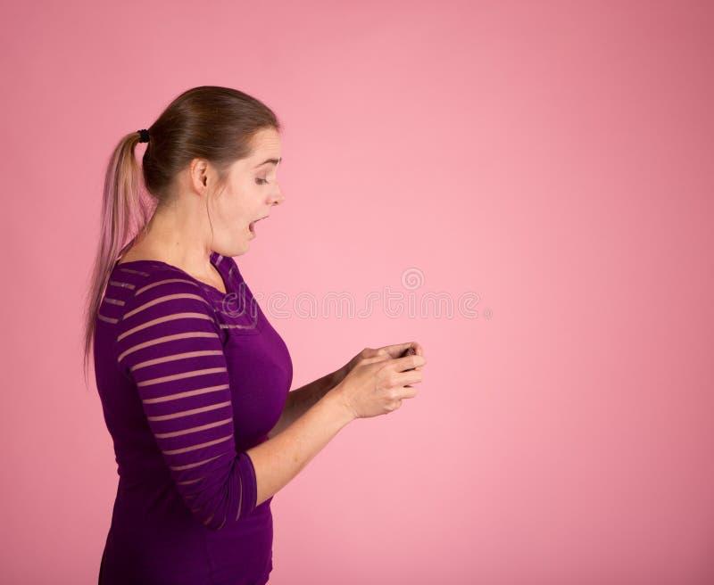发短信在与惊奇的神色的桃红色的妇女 库存照片