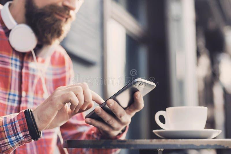 发短信在他的智能手机的年轻人在城市 关闭快乐的成人使用手机在咖啡馆 免版税库存图片
