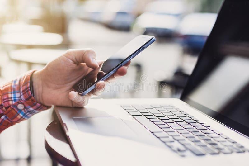 发短信在他的智能手机的年轻人在城市 关闭快乐的成人使用手机在咖啡馆 免版税库存照片