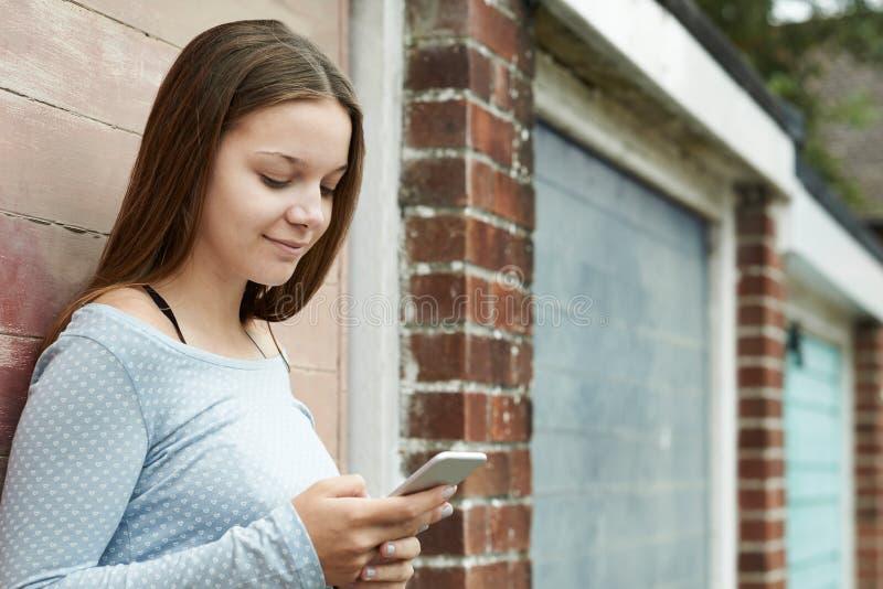 发短信在城市布局的手机的十几岁的女孩 库存照片