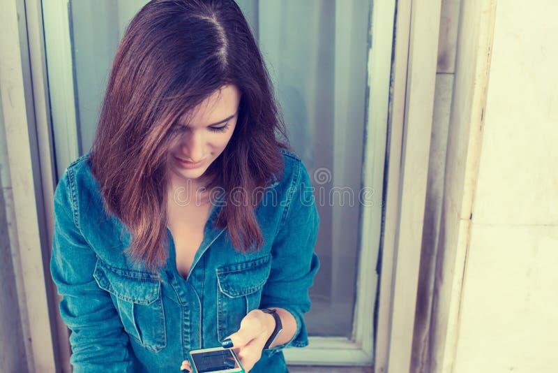 发短信在她巧妙的电话的微笑的妇女 免版税库存图片