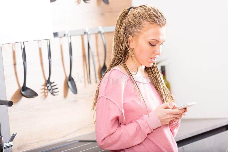 发短信在她的机动性的年轻白肤金发的妇女 库存图片