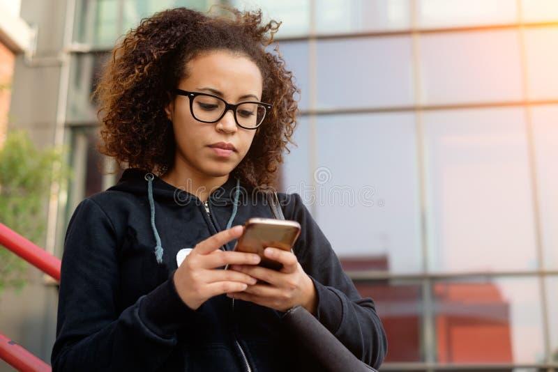 发短信在她的电话的年轻千福年的女孩 库存图片