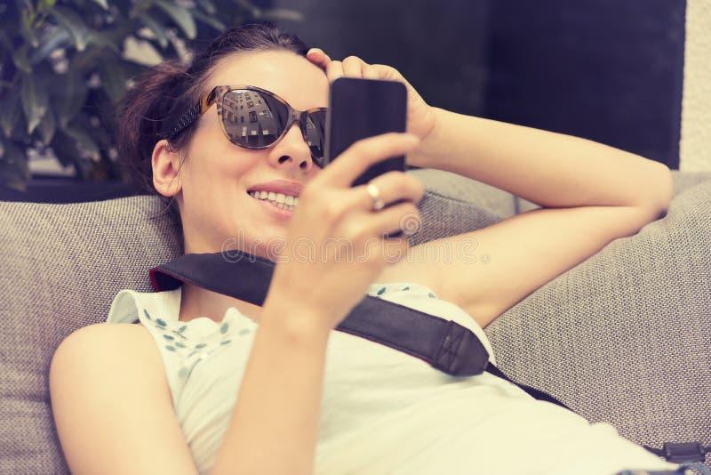 发短信在巧妙的电话的愉快的女孩在旅馆餐馆大阳台休息室 免版税库存图片