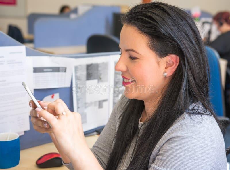 发短信在手机的微笑的妇女在工作 库存照片