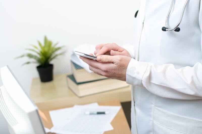 发短信在智能手机的一位女性医生 免版税库存图片