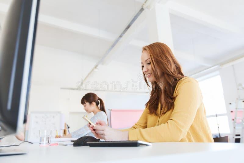 发短信在智能手机的女实业家在办公室 库存照片