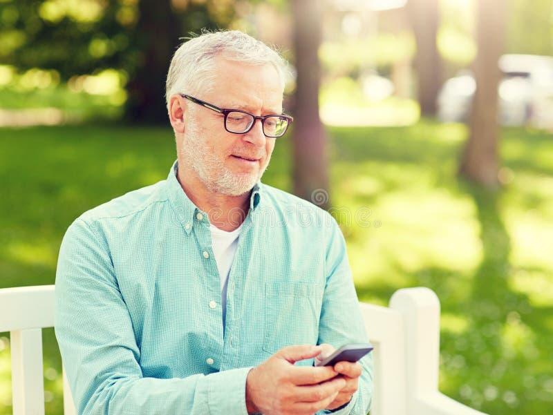 发短信在智能手机的愉快的老人在夏天 库存图片