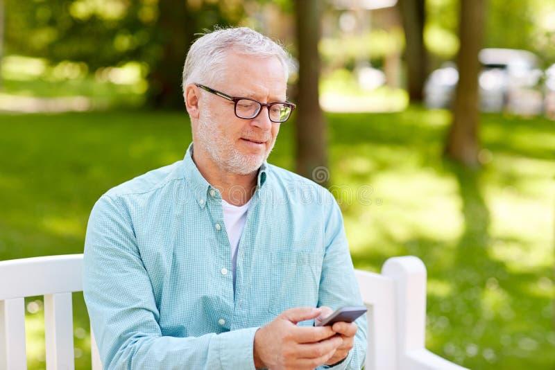 发短信在智能手机的愉快的老人在夏天 免版税库存图片
