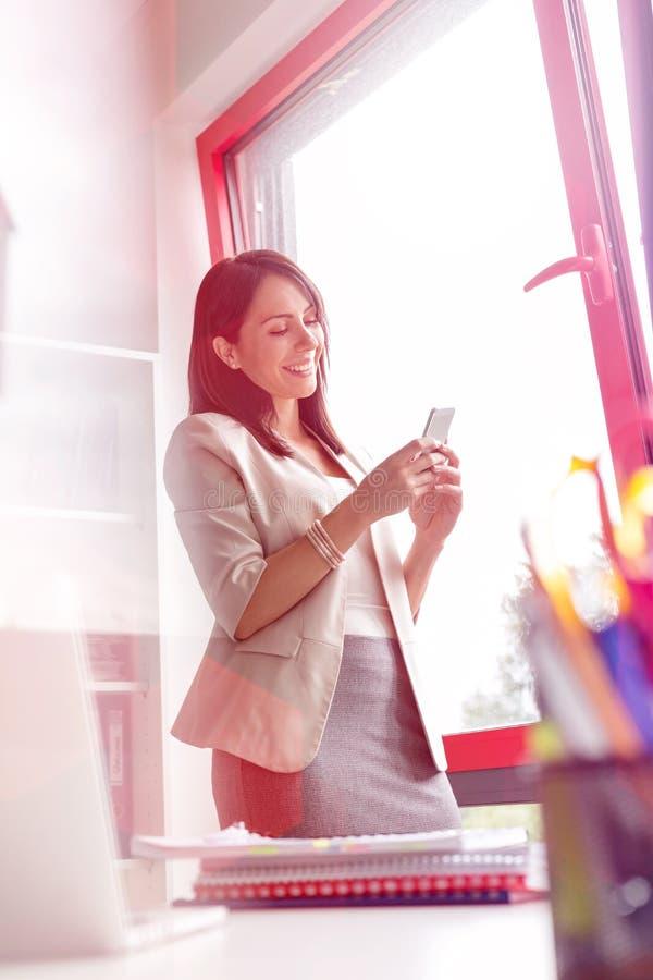 发短信在智能手机的确信的女实业家在办公室 免版税库存图片