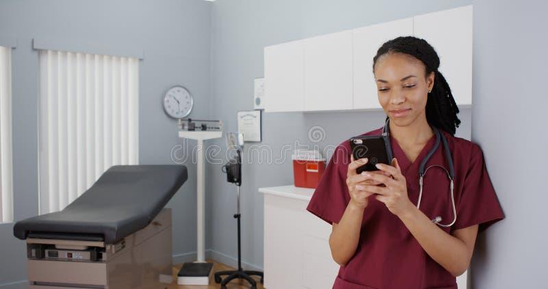 发短信在智能手机的黑人妇女护士 免版税图库摄影