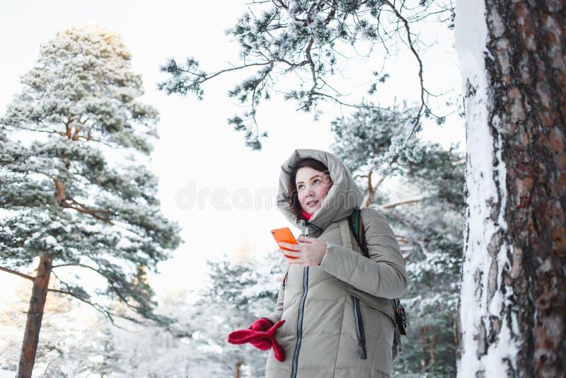 发短信在橙色智能手机的快乐的妇女在旅行期间对森林在冬天 穿温暖的夹克的深色的模型 免版税图库摄影