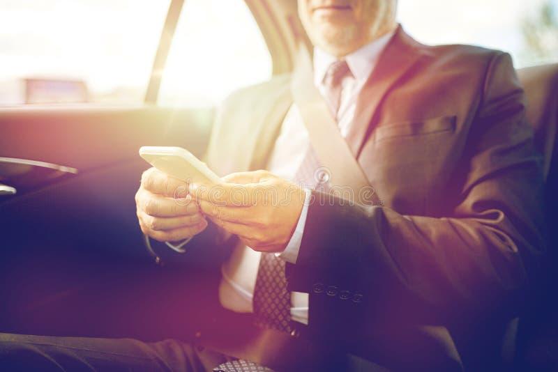 发短信在汽车的智能手机的资深商人 免版税库存照片