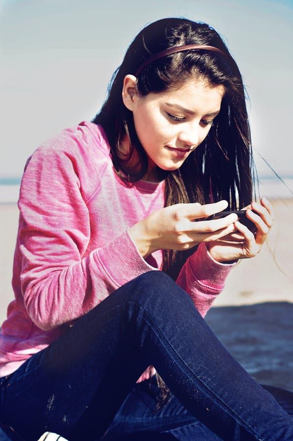 发短信在海滩的少年 免版税图库摄影