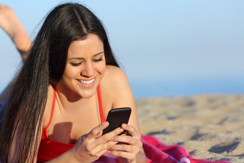 发短信在海滩的巧妙的电话的青少年的女孩 免版税库存照片