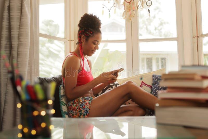 发短信在电话和微笑的年轻黑人妇女 免版税库存图片