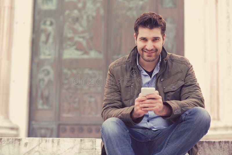 发短信在电话的人微笑对照相机 库存照片