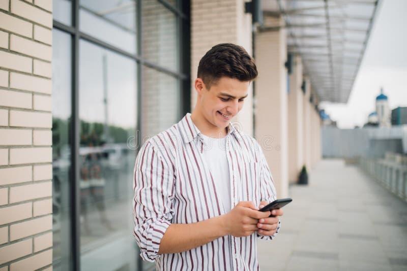 发短信在电话的人 使用智能手机微笑的愉快的外部办公楼的偶然都市专业企业家 室外portr 免版税库存图片