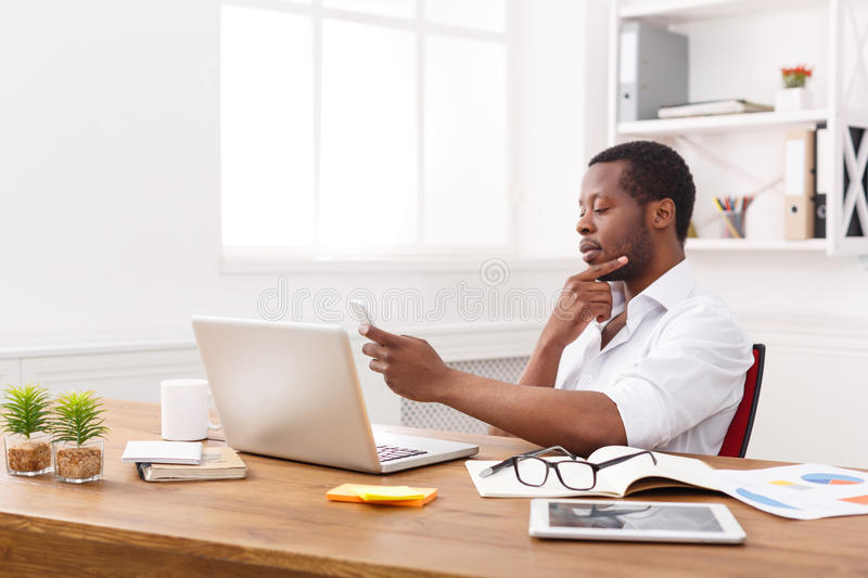 发短信在电话的周道的非裔美国人的商人,当研究膝上型计算机时 库存照片