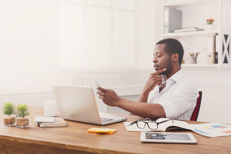 发短信在电话的周道的非裔美国人的商人,当研究膝上型计算机时 免版税图库摄影