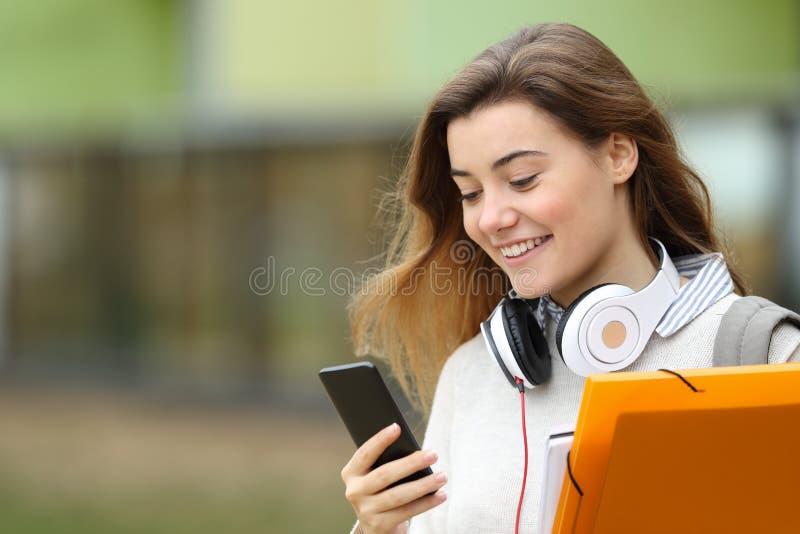 发短信在电话的学生在大学附近 库存图片