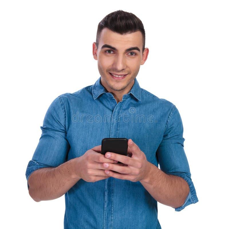 发短信在电话的年轻偶然人画象  免版税库存照片