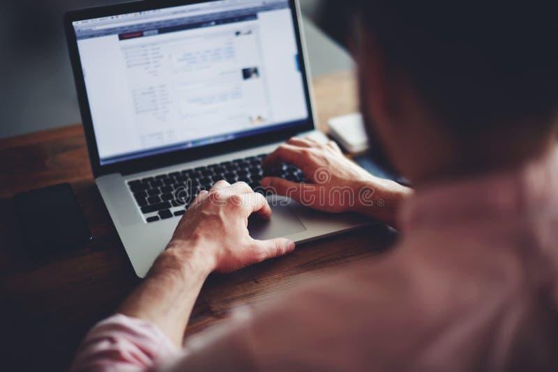 发短信在计算机上的年轻男学生坐在木桌上 库存照片