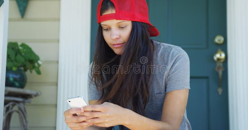发短信在门廊的电话的愉快的混合的族种妇女 库存照片
