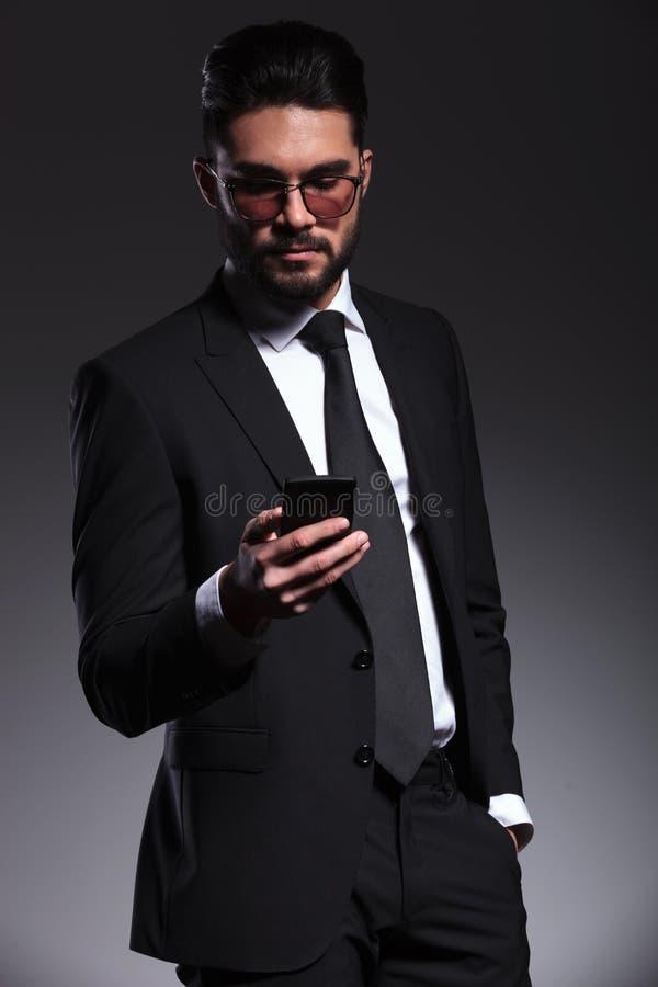 发短信在他的智能手机的年轻商人 免版税库存照片