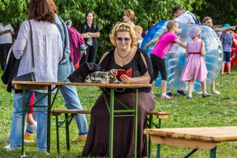 发短信微笑的弯曲的妇女佩带的太阳镜,当坐由桌时 操场的一名单身妇女 库存图片