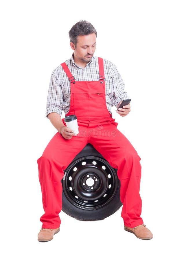 发短信或浏览在智能手机的汽车机械师 库存图片