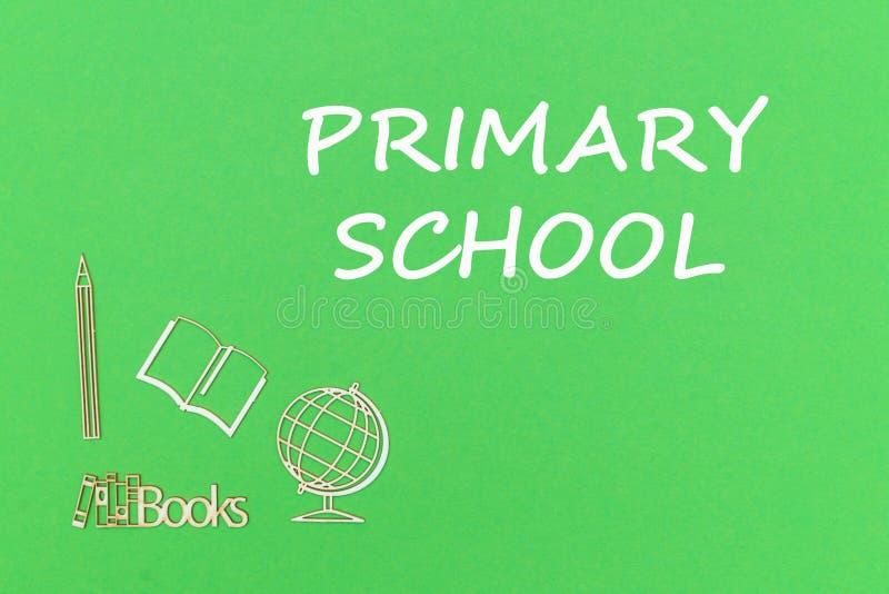 发短信给小学,在绿色背景的学校用品木缩样 免版税库存图片