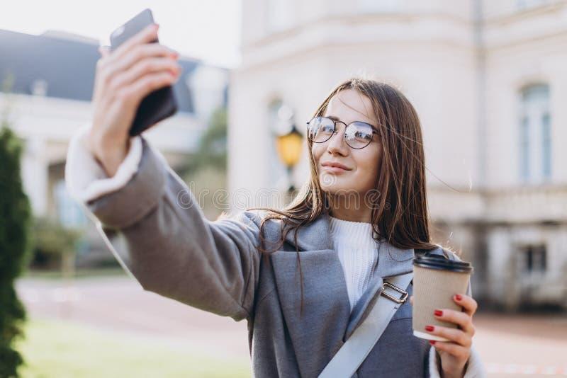 发短信给或使用智能手机的年轻女人 库存图片