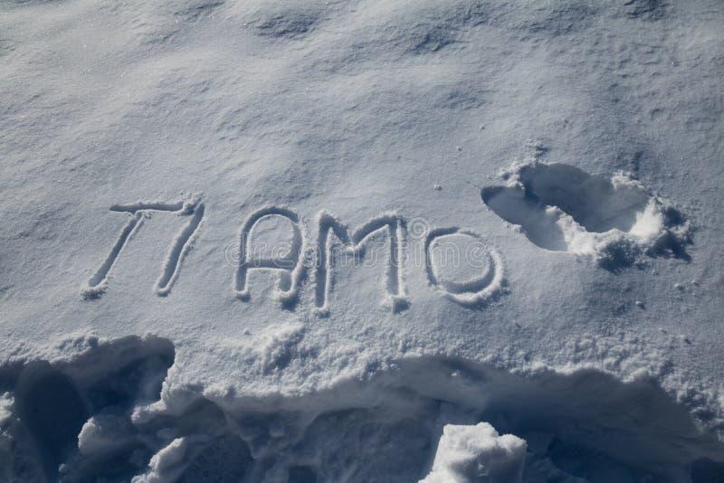 发短信给词`钛amo `在多雪的背景写的意大利语手上 免版税库存图片