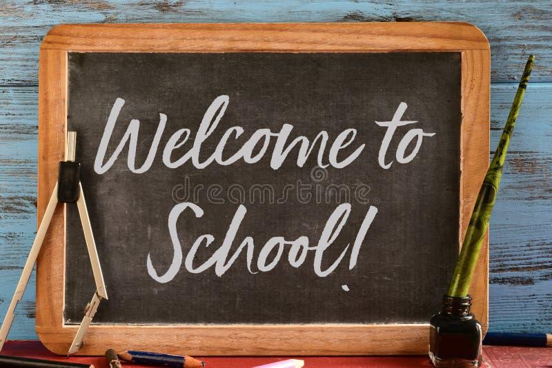 发短信给欢迎到在黑板写的学校 免版税图库摄影