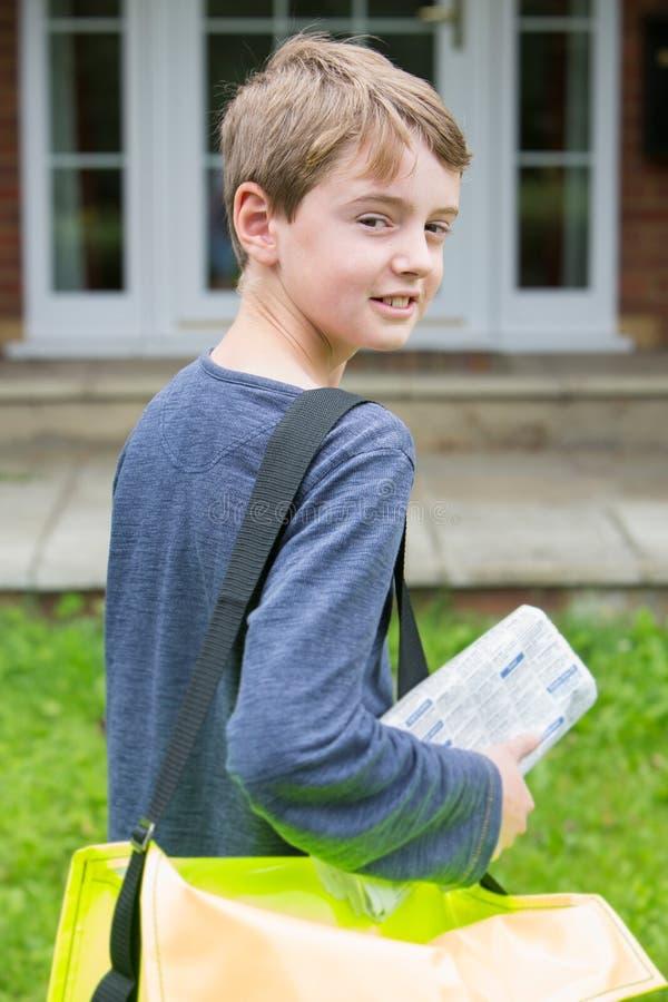 发表报纸的十几岁的男孩画象到议院 图库摄影