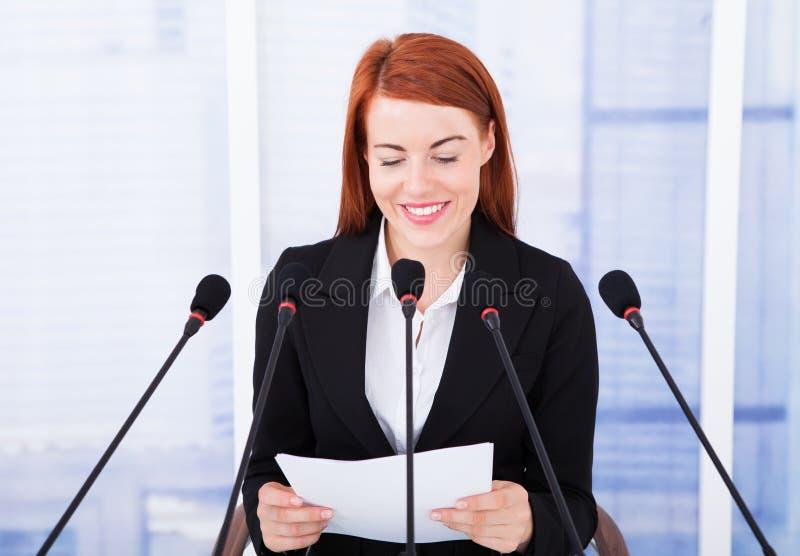 发表讲话的微笑的女实业家在会议 免版税图库摄影