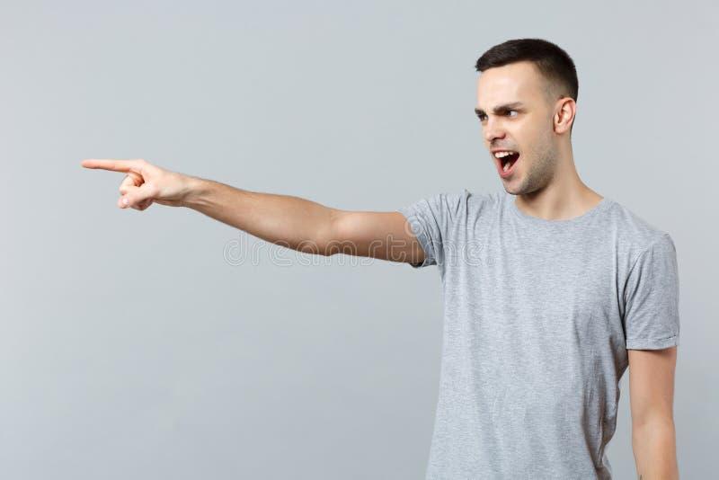 发誓恼怒的被激怒的年轻人画象便服的指向在灰色墙壁上在旁边隔绝的食指 免版税图库摄影