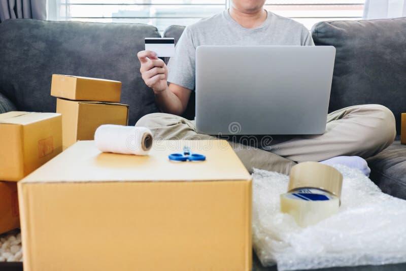 发货的小企业小包对客户,年轻人由信用接受了网络购物小包打开的箱子和买的项目 免版税库存图片