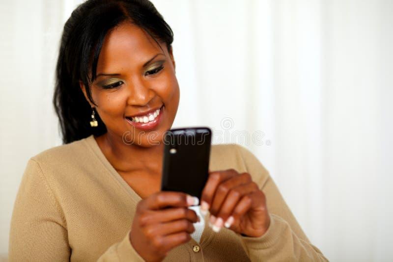 发送正文消息的可爱的黑人妇女 免版税库存照片