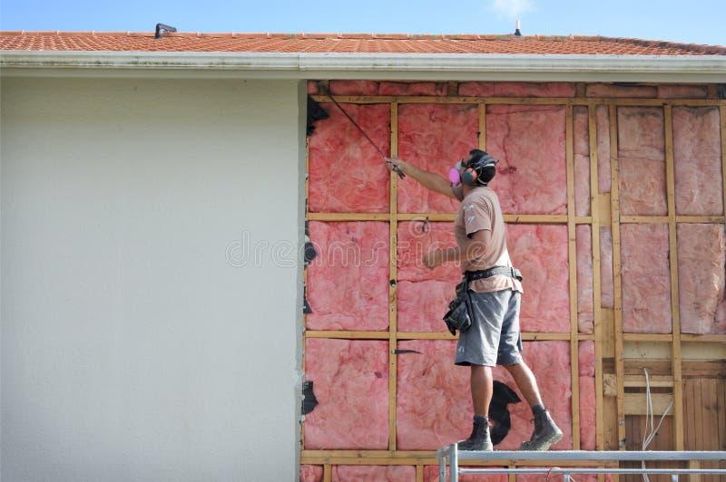 取消一种老玻璃纤维墙壁绝缘材料的建造者从buildi 免版税库存图片