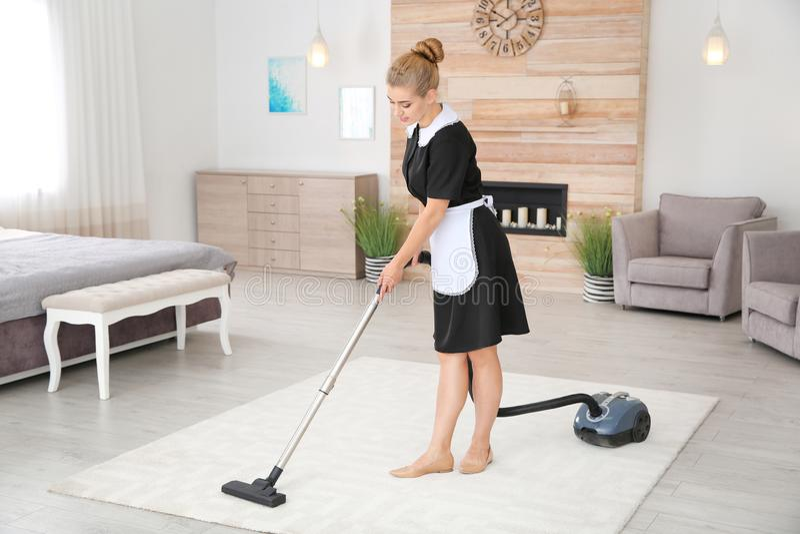 取消土的年轻女服务生从地毯与吸尘器 库存图片