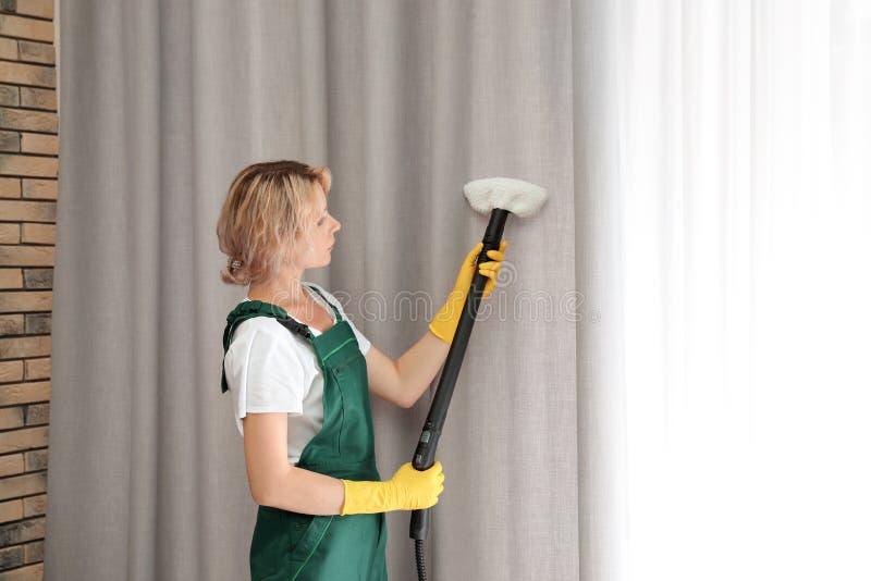 取消尘土的女性管理员从帷幕与蒸汽擦净剂 免版税库存照片