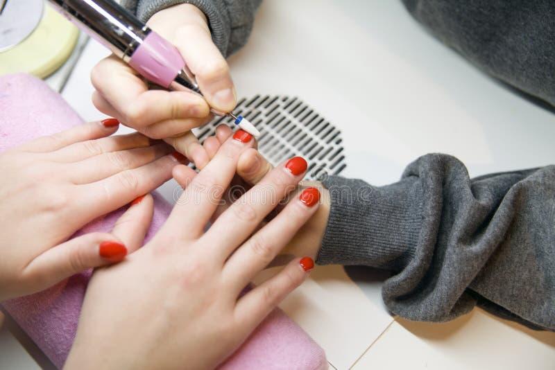 取消老指甲油,修指甲 碾碎钉子 去除钉子板材与一台铣床 免版税库存图片
